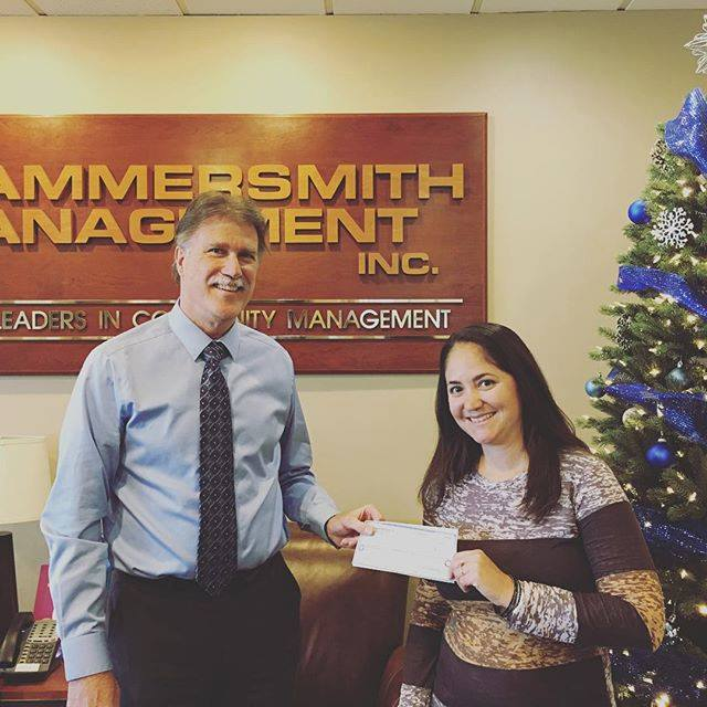 Hammersmith employee giving a check to charity